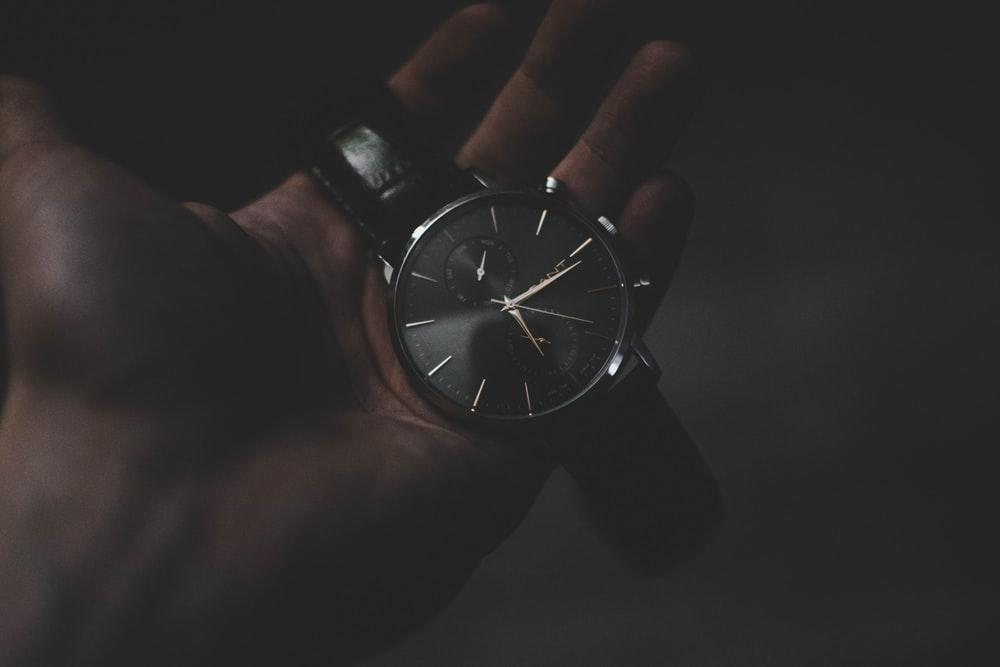 person holding watch pointing at 6:17