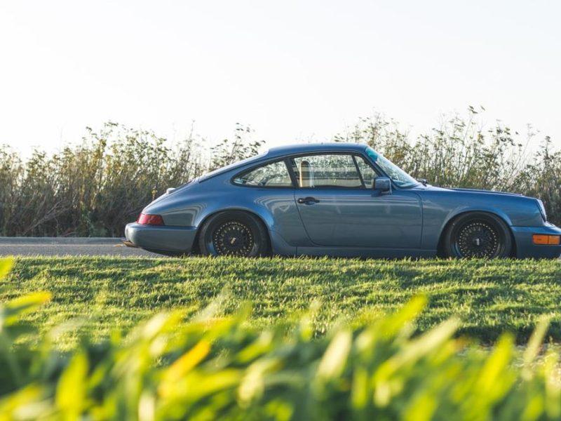 blue Porsche 911 parked beside road