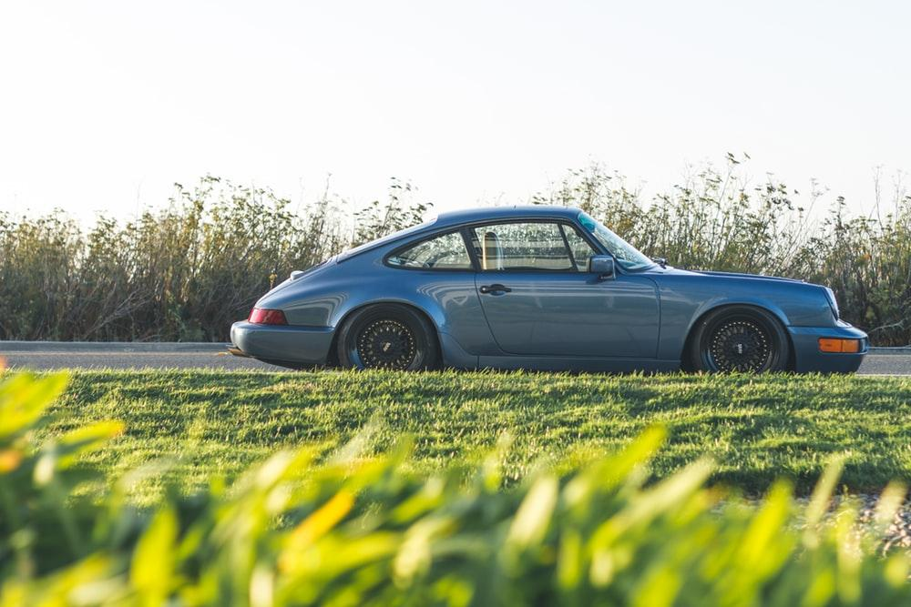 blue Porsche 911 parked beside road